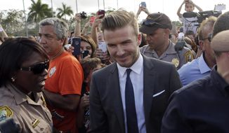FILE - In this Feb. 5, 2014, file photo, David Beckham, surrounded by Miami-Dade police officers, fans and reporters, arrives at Kendall Soccer Park to visit and greet South Florida soccer fans and players in Miami.  David Beckham may finally be moving closer to bringing an MLS team to Miami. County commissioners are planning to vote Tuesday, June 6, 2017, on a deal that would give Beckham the last piece of land he needs for a stadium site. (AP Photo/Alan Diaz, File)