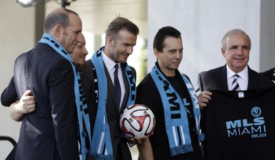 FILE - In this Feb. 5, 2014, file photo, former English soccer star David Beckham, third from left, poses with MLS Commissioner Don Garber, left, Miami-Dade County mayor Carlos Gimenez, right, and soccer fans with the Southern Legion at a news conference where he announced he will exercise his option to purchase a Major League Soccer expansion team, in Miami. David Beckham may finally be moving closer to bringing an MLS team to Miami. County commissioners are planning to vote Tuesday, June 6, 2017, on a deal that would give Beckham the last piece of land he needs for a stadium site. (AP Photo/Lynne Sladky, File)