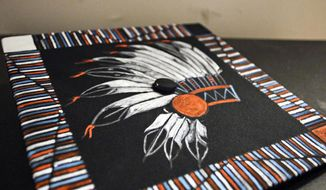 """In this June 2, 2017, photo Zephrey Holloway's decorated mortarboard is displayed at Flathead High School's graduation in Kalispell, Mont. An administrator at the school prevented Holloway from wearing the mortarboard, painted by his grandmother, despite a new state law that allows Native American students to wear such regalia at special occasions. Principal Peter Fusaro issued an apology Monday, June 5, 2017, saying a school policy that disallowed graduates from using """"tape, glitter, leis, bouquets or any other adornments"""" on caps and gowns was applied incorrectly. (Greg Lindstrom/Flathead Beacon via AP)"""