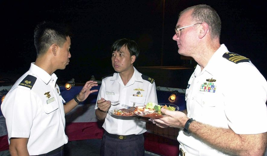 "In this July 4, 2001, photo provided by the U.S. Department of Defense shows U.S. Navy Commander Dave Kapaun, right, with Republic of Singapore Navy Major Danny Tan, left, and Republic of Singapore Major H .C. Lim at a reception on board the U.S. Navy dock landing ship USS Rushmore during the seventh annual Cooperation Afloat Readiness and Training (CARAT) Exercise. Retired U.S. Navy Commander Kapaun is scheduled to plead guilty Tuesday, June 6, 2017, in Honolulu, Hawaii, in federal court to lying about his relationship with Leonard Francis, nicknamed ""Fat Leonard"" in a growing corruption scandal involving the Malaysian defense contractor. (Kevin H. Tierney/U.S. Department of Defense via AP)"