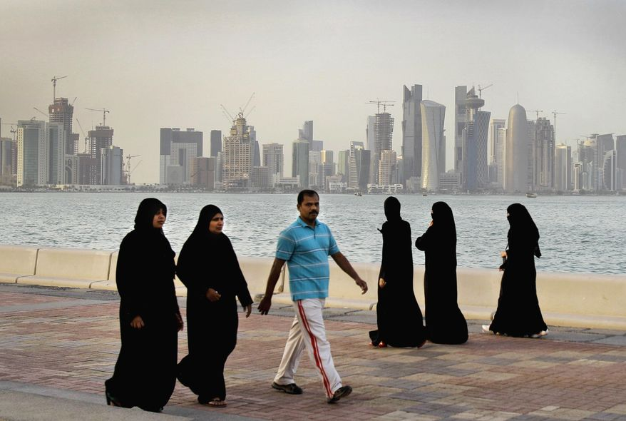 FILE- In this Saturday, April 7, 2012 file photo, the new high-rise buildings of downtown Doha, photographed in the background as Qatari women and a man walk by the sea in Doha, Qatar. Qatar, now facing a diplomatic crisis with other Arab nations, is a small country with a big history of turmoil and coups as it became one of the world's top suppliers of natural gas and now plans to host the 2022 FIFA World Cup. (AP Photo/Kamran Jebreili, File)