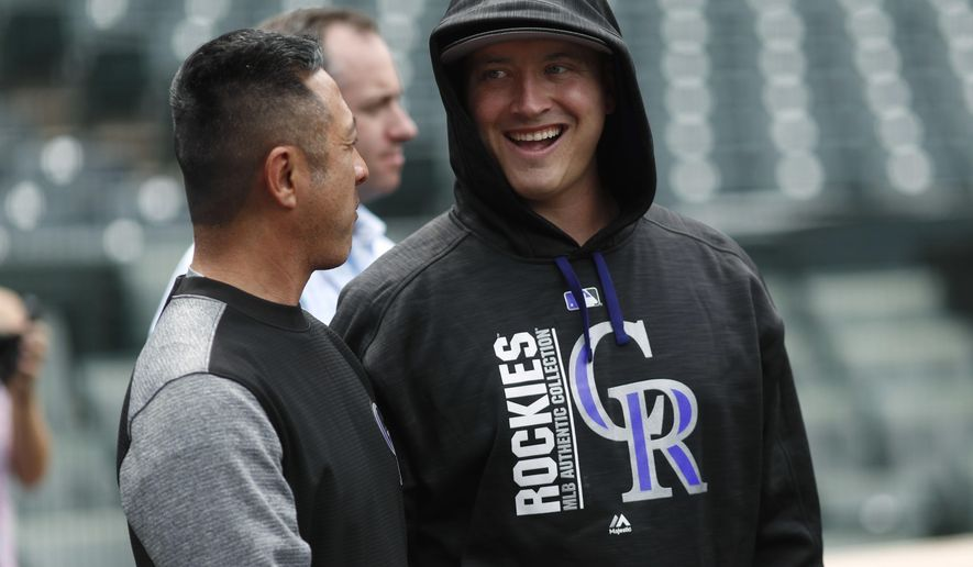 Injured Colorado Rockies starting pitcher Chad Bettis, right, jokes with Scott Murayama, the team's rehabilitation coordinator/athletic trainer, Tuesday, June 6, 2017, in Denver. Bettis has been battling testicular cancer for about a year. (AP Photo/David Zalubowski)