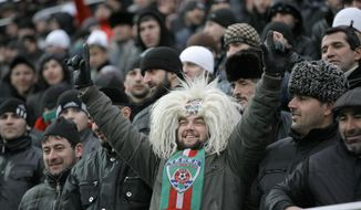 FILE - In this Tuesday, March 8, 2011 file photo, a Chechen soccer fan wears a traditional Chechen hat and a scarf in colors of Chechen soccer club Terek Grozny, during a friendly game between Chechnya and Brazil in the stadium in Grozny. A Russian league soccer club in formerly war-torn Chechnya is to be renamed after the regional leader's dead father. Terek Grozny CEO Akhmed Aidamirov said Tuesday, June 6, 2017 the club, which has previously won the Russian Cup, will be renamed Akhmat Grozny after Akhmat Kadyrov, the father of current regional leader Ramzan Kadyrov. (AP Photo/Musa Sadulayev, file)