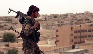 "FILE - In this Sunday, April 30, 2017, file photo, provided by the Syria Democratic Forces (SDF), shows a fighter from the SDF carrying weapons as he looks toward the northern town of Tabqa, Syria. A U.S. military official says the offensive against the Islamic State group's de facto capital, Raqqa ""will be long and difficult."" Lt. Gen. Steve Townsend, the top U.S. commander in Iraq, says the assault by the Syrian Democratic Forces will deliver a decisive blow to the idea of IS ""as a physical caliphate."" The Kurdish-led force launched an offensive to capture Raqqa on Tuesday.(Syrian Democratic Forces, via AP, File)"