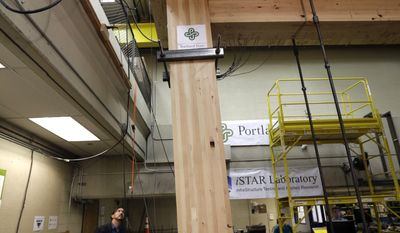 FILE - In this Nov. 15, 2016, file photo, Lever Architecture founder Thomas Robinson looks over a strength test on cross-laminated timber beams, or CLT, at Portland State University in Portland, Ore. City officials in Portland have approved a construction permit for the first all-wood high-rise building in the nation. The building uses the new technology called cross-laminated timber that tests have shown can withstand the worst earthquakes. Developers worked with scientists at Portland State University and Oregon State University to prove through testing that the materials meet all building and fire safety codes. (AP Photo/Don Ryan, file)