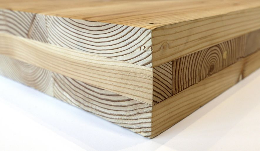 FILE--This Nov. 15, 2016, file photo shows a piece of cross-laminated timber, or CLT , in Portland, Ore. City officials in Portland have approved a construction permit for the first all-wood high-rise building in the nation. The building uses the new technology called cross-laminated timber that tests have shown can withstand the worst earthquakes. Developers worked with scientists at Portland State University and Oregon State University to prove through testing that the materials meet all building and fire safety codes. (AP Photo/Don Ryan, file)