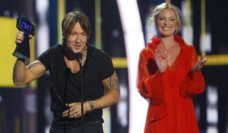 "Keith Urban accepts the award for male video of the year for ""Blue Ain't Your Color"" at the CMT Music Awards at Music City Center on Wednesday, June 7, 2017, in Nashville, Tenn. Looking on in background right is presenter Katherine Heigl. (Photo by Wade Payne/Invision/AP)"