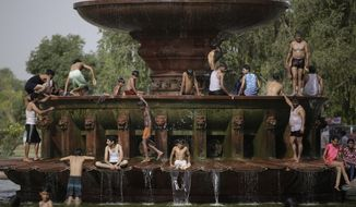 Indians cool off themselves at a fountain near the India Gate monument on a hot day in New Delhi, India, Tuesday, June 6, 2017. (AP Photo/Altaf Qadri)