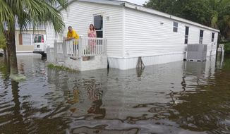 John and Cammie Harding look out onto flooded SW 5th St., in Sunshine Village, Wednesday, June 7, 2017, in Davie, Fla. Several days of constant rain has caused flooding throughout Broward and Palm Beach Counties. (Joe Cavaretta/South Florida Sun-Sentinel via AP)