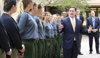 Arizona Gov. Doug Ducey talks to members of the Arizona Department of Corrections' only female fire crew at the state Capitol in Phoenix, Ariz., Tuesday, April 11, 2017. A relatively wet spring means wildfire dangers will be much higher in Arizona's southern deserts and grasslands as they eventually dry out, leaving the state with mixed anticipation for the upcoming fire season. (AP Photo/Bob Christie)