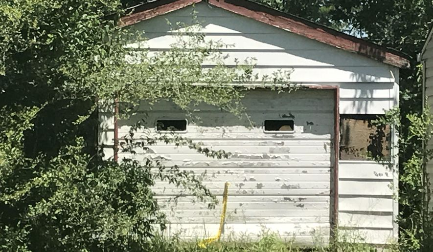 Trees grow in front of the entrance of a garage Tuesday, June 6, 2017, where the remains of a 7-year-old child was found in Centreville, Ill. A Las Vegas woman told investigators Tuesday that her dead child had been in a southern Illinois home for two years, and authorities later found human remains in the vacant house, according to authorities. Centreville police Sgt. DeMarius Thomas Sr. told the St. Louis Post-Disaptch that police believe the child was killed in nearby Belleville, Ill, and dumped in the garage. (Christine Byers/St. Louis Post-Dispatch via AP)