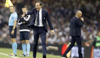 Juventus head coach Massimiliano Allegri shouts as Real Madrid's head coach Zinedine Zidane walks behind during the Champions League final soccer match between Juventus and Real Madrid at the Millennium stadium in Cardiff, Wales Saturday June 3, 2017. (AP Photo/Frank Augstein)