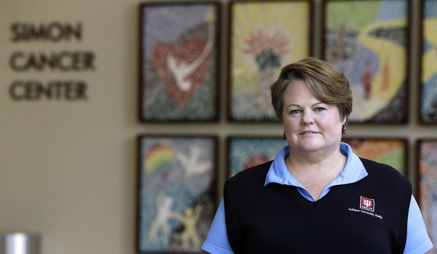 Margie Barton, a financial counselor at the IU Health Melvin and Bren Simon Cancer Center, is photographed in the lobby of the hospital, Wednesday, June 7, 2017, in Indianapolis. Barton helps to explain how health benefits works once patients arrive at the hospital. Shrinking insurance coverage and soaring treatment costs can swamp patients with piles of unexpected bills. (AP Photo/Darron Cummings)