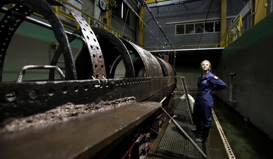 Conservator Anna Funke stands next to the H.L. Hunley in the Warren Lasch Conservation Center in North Charleston, S.C., Wednesday, June 7, 2017. For years, two scientists have been painstakingly cleaning a century and a half of sand, sediment and corrosion from the first submarine in history to sink an enemy warship. (Michael Pronzato/The Post And Courier via AP)