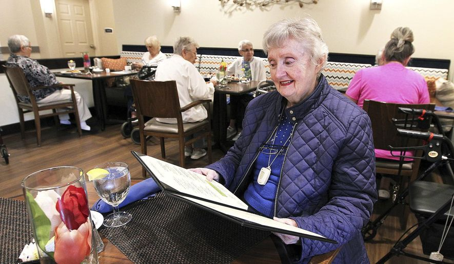 In this May 9, 2017 photo, Pat Clingenpeel looks over the lunch menu at the first floor  bistro at Clarendale of Algonquin senior living community in Algonquin, Ill. The facility offers independent living, assisted living, and memory care. As McHenry County gets grayer, developers are responding by building age-restricted communities for those older than 55 as other segments of the housing market lag. (H. RIck Bamman/Northwest Herald via AP)/Northwest Herald via AP)