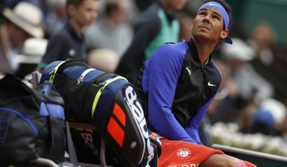 Spain's Rafael Nadal looks at rain clouds in his quarterfinal match against Spain's Pablo Carreno Busta at the French Open tennis tournament at the Roland Garros stadium, in Paris, France. Wednesday, June 7, 2017. (AP Photo/Petr David Josek)