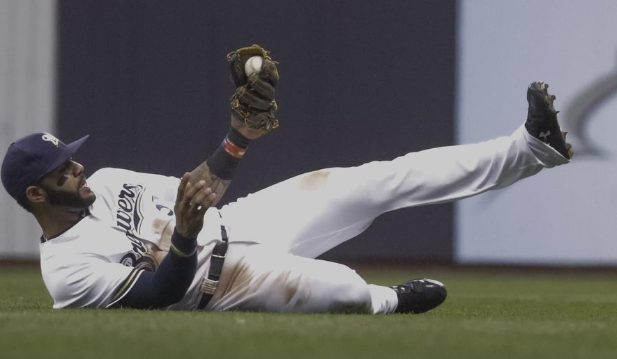 Milwaukee Brewers' Jonathan Villar makes a diving catch on a ball hit by San Francisco Giants' Buster Posey during the fifth inning of a baseball game Wednesday, June 7, 2017, in Milwaukee. (AP Photo/Morry Gash)