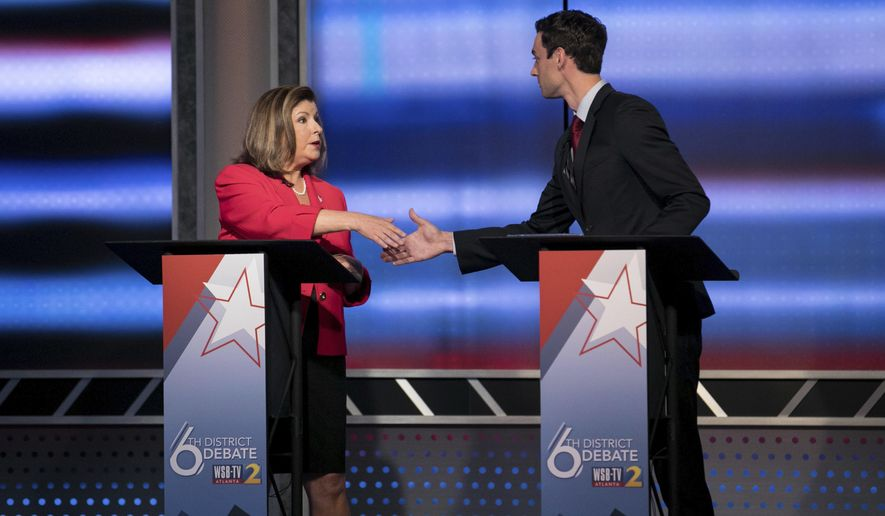 Candidates in Georgia's 6th Congressional District race Republican Karen Handel, left, and Democrat Jon Ossoff shake hands after a debate Tuesday, June 6, 2017, in Atlanta.  The two meet in a June 20 special election.(Branden Camp/Atlanta Journal-Constitution via AP)