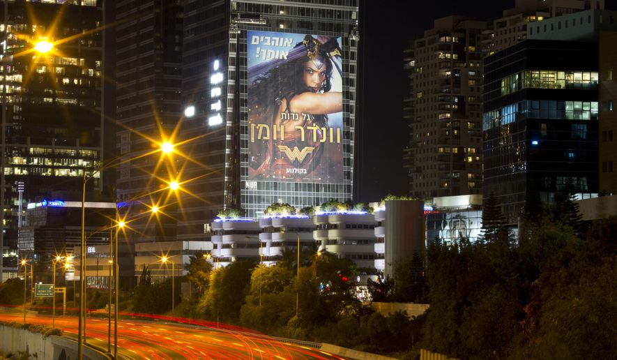 This Wednesday, June 6, 2017 photo, taken with a long exposure, shows a billboard promoting the film, Wonder Woman, in Tel Aviv, Israel. For a country that takes pride in even the smallest successes of its international celebrities, the debut of Wonder Woman has sparked an Israeli lovefest for homegrown hero Gal Gadot. (AP Photo/Ariel Schalit)