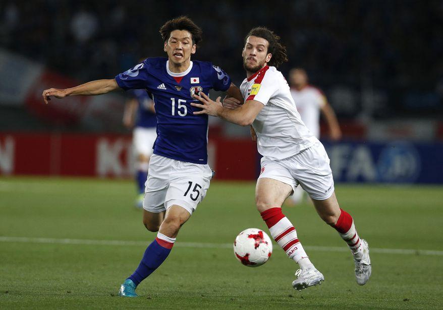 Japan's Yuya Osako, left, and Syria's Omro Al Midani vie for the ball during their Kirin Challenge Cup international friendly soccer match in Tokyo, Wednesday, June 7, 2017.(AP Photo/Shuji Kajiyama)
