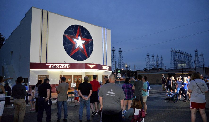ADVANCE FOR USE MONDAY, JUNE 12 - In this Wednesday, May 31, 2017 photo, guests gather in front of the Texan after a relighting ceremony for the 73 year old theater's facade in downtown Kilgore, Texas. (Les Hassell/The News-Journal via AP)