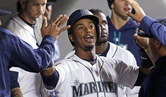 FILE - In this May 2, 2017, file photo, Seattle Mariners' Jean Segura is congratulated after scoring against the Los Angeles Angels during the third inning of a baseball game, in Seattle. The Mariners have agreed with shortstop Jean Segura on a new five-year contract that brings stability to what has been a position of flux for more than a decade. Terms of the contract were not released Wednesday, June 7, 2017, but reports have the deal being worth $70 million. (AP Photo/Elaine Thompson, File)