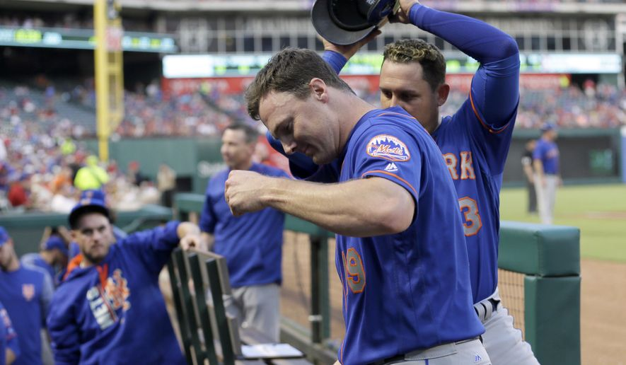 New York Mets' Jay Bruce (19) has his helmet removed by Asdrubal Cabrera, rear, as they celebrate Bruce's two-run home run against the Texas Rangers during the fourth inning of a baseball game, Wednesday, June 7, 2017, in Arlington, Texas. (AP Photo/Tony Gutierrez)