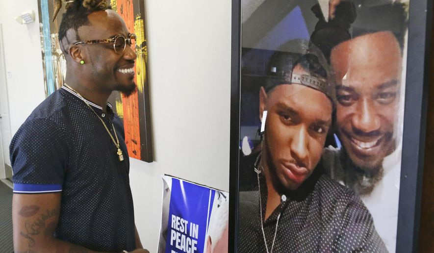 In this Thursday, May 4, 2017, photo, Demetrice Naulings, a survivor of the Pulse nightclub shooting, looks at a photo of himself with friend Eddie Justice, at his apartment complex, in Orlando, Fla. Justice died during the shooting. (AP Photo/John Raoux)