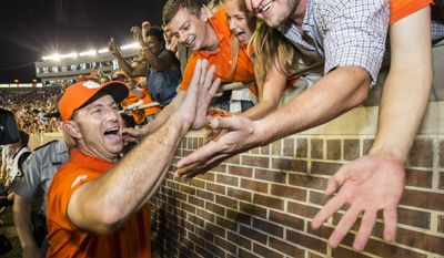 FILE - In this Saturday, Oct. 29, 2016, photo, Clemson coach Dabo Swinney celebrates the team's 37-34 win over Florida State in an NCAA college football game in Tallahassee, Fla. Not many college football fans outside of Alabama and Ohio State are totally content with their coach. And contentment can be fleeting as Michigan State fans are finding out now. These days Clemson fans are crazy about Swinney and Stanford supporters are cool with David Shaw. (AP Photo/Mark Wallheiser, File)