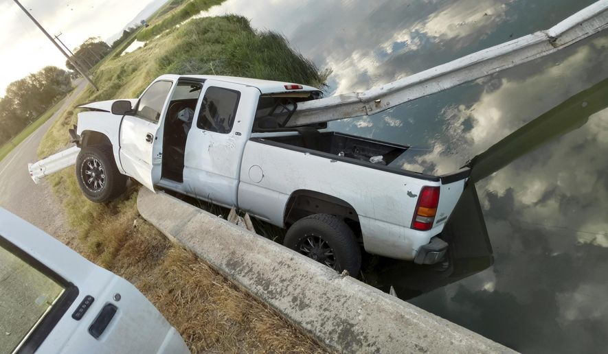 This Sunday, June 4, 2017 photo shows where a stolen pickup truck was found impaled on about 30 feet of guard rail over a canal near Aberdeen in eastern Idaho. A worker with The Aberdeen-Springfield Canal Company discovered the white GMC Sierra pickup Sunday morning, run completely through by several yards of steel guard rail and left partially dangling in the water. The driver was nowhere to be found. (Blake Healy/Aberdeen-Springfield Canal Company via AP)