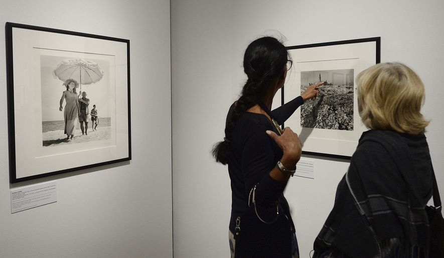 Visitors get a preview of a new exhibition at the National Museum in Warsaw featuring 150 years of Hungarian photography, in Warsaw, Poland, on Wednesday June 7, 2017. Hungarian photographers were among some of the leading practitioners of the genre throughout the 20th century, and include figures such as war photographer Robert Capa and Brassai, who are featured in the show. (AP Photo/Czarek Sokolowski)