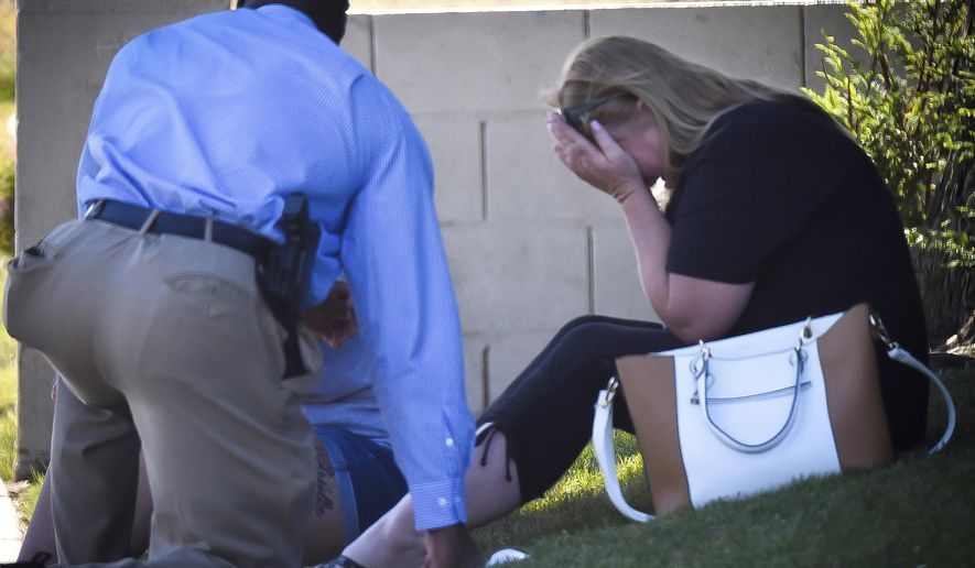 A Fresno police detective talks to family members of the man shot to death at a house where an officer involved shooting occurred Wednesday, June 7, 2017. Police say a suspected gang member was shot and killed early Wednesday after he fired a least 75 rounds at officers with a high-powered rifle. Officers were first called to the home following reports of gunfire from neighbors. (John Walker/Fresno Bee via AP)
