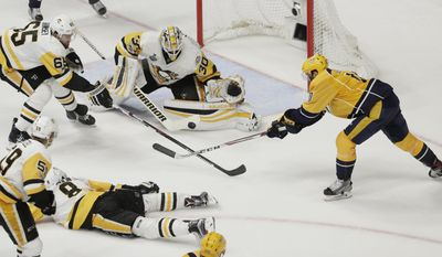 Nashville Predators center Colton Sissons (10) shoots against Pittsburgh Penguins goalie Matt Murray (30) and defenseman Ron Hainsey (65) during the third period in Game 4 of the NHL hockey Stanley Cup Finals Monday, June 5, 2017, in Nashville, Tenn. (AP Photo/Mark Humphrey)