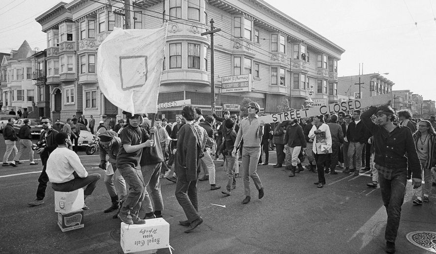 ADVANCE FOR USE TUESDAY, JUNE 13, 2017 AND THEREAFTER-FILE - In this April 3, 1967 file photo, people parade up and down the streets of the Haight-Ashbury district in San Francisco. They came for the music, the mind-bending drugs, to resist the Vietnam War and 1960s American orthodoxy, or simply to escape summer boredom. And they left an enduring legacy. Fifty years ago, throngs of American youth descended on San Francisco to join a cultural revolution. (AP Photo/Robert W. Klein, File)