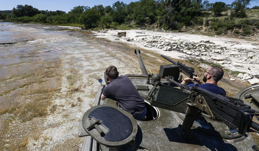 ADVANCED FOR USE MONDAY, JUNE 12 AND THEREAFTER Spencer Jones, left, and his cousin, Casey Jones, right, watch as their family member drives a Sherman Easy 8 tank through a river during an Allies and Axis all-day DriveTanks.com experience at Ox Ranch, Wednesday, May 24, 2017 in Uvalde, Texas. At the ranch, people can drive and shoot the main canon of vintage WWII-era tanks and fire a variety of machine guns, artillery and other heavy guns. (Michael Ciaglo/Houston Chronicle via AP)