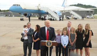President Donald Trump speaks about health care at Cincinnati Municipal Lunken Airport in Cincinnati, Ohio, Wednesday, June 7, 2017. Shown are PlayCare co-owner Rays Whalen, left, and CSS Distribution Group President Dan Withrow and their families.  (AP Photo/Andrew Harnik)