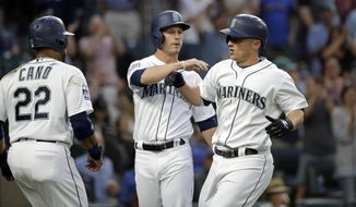 Seattle Mariners' Kyle Seager, right, is greeted by Robinson Cano (22) and Boog Powell on Seager's three-run home run against the Minnesota Twins in the fourth inning of a baseball game Tuesday, June 6, 2017, in Seattle. (AP Photo/Elaine Thompson)