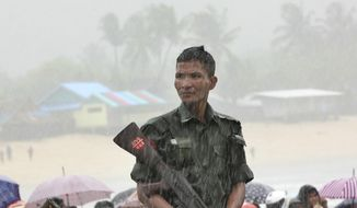 A soldier weathers monsoon rain as bodies are recovered of the waters off San Hlan village, in Laung Lone township, southern Myanmar, Thursday, June 8, 2017. Fishermen have joined navy and air force personnel in recovering bodies and aircraft parts from the sea off Myanmar, where a military plane carrying 122 people including 15 children crashed a day earlier. (AP Photo/Esther Htusan)