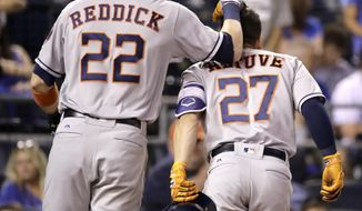 Houston Astros' Josh Reddick (22) celebrates with Jose Altuve (27) after Altuve hit a two-run home run during the ninth inning of a baseball game against the Kansas City Royals on Thursday, June 8, 2017, in Kansas City, Mo. (AP Photo/Charlie Riedel)