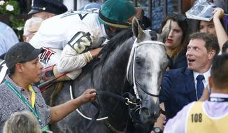 FILE - In this June 11, 2016, file photo, jockey Irad Ortiz Jr., riding Creator, talks with Bobby Flay, part owner of the horse, after Creator won the Belmont Stakes horse race at Belmont Park in New York. Flay purchased 25 percent interest in J Boys Echo on Wednesday, June 7, 2017, before the draw that assigned post positions for Saturday's $1.5 million race. The other 75 percent belongs to Albaugh Family Stable. (AP Photo/Kathy Willens, File)