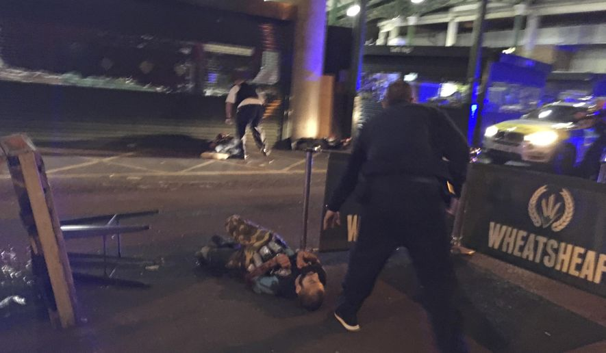 In this image provided by Gabriele Sciotto taken on Saturday, June 3, 2017, one of the suspects from the London Bridge attack, wearing what appear to be canisters strapped to his chest, lies on the ground after being shot by police outside Borough Market in London. Dramatic footage from London's Borough Market shows three attackers viciously stabbing a man just before police converge and shoot them all dead. The footage, believed to be from a surveillance camera, shows the final moments of the attack that started when the three rammed a van into pedestrians on busy London Bridge late Saturday. (Gabriele Sciotto via AP)