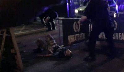In this image made from video provided by Gabriele Sciotto taken on Saturday, June 3, 2017, one of the suspects from the London Bridge attack, wearing what appear to be canisters strapped to his chest, lies on the ground after being shot by police outside Borough Market in London. Dramatic footage from London's Borough Market shows three attackers viciously stabbing a man just before police converge and shoot them all dead. The footage, believed to be from a surveillance camera, shows the final moments of the attack that started when the three rammed a van into pedestrians on busy London Bridge late Saturday. (Gabriele Sciotto via AP)