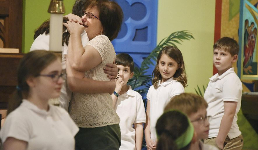 In this June 2, 2017 photo, Diann Ranallo, first grade teacher at St. Ursula School, tears up as several students made a presentation at the awards ceremony, after Mass, on the last day of school for St. Ursula School, in Hampton Township, Pa. Ranallo was retiring. The school is closing and being consolidated. (Darrell Sapp/Pittsburgh Post-Gazette via AP)