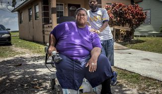 This photo taaken May 30, 2017, shows Darryl Henderson, left, a formerly homeless resident of South Bay, sits in his motorized wheelchair next to his childhood friend that he is temporarily living with, Taurance Lovely. (Damon Higgins /Palm Beach Post via AP)