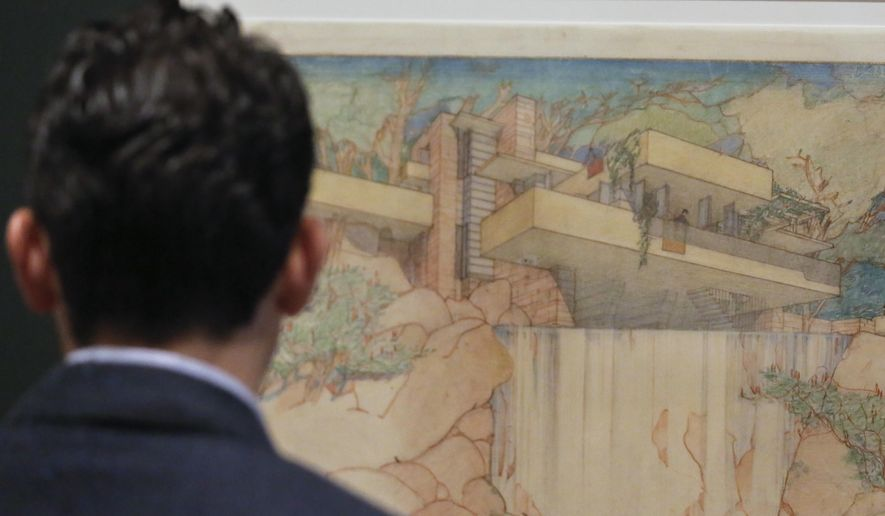 """A visitor reviews a colored pencil drawing of architect Frank Lloyd Wright's Fallingwater house, during the press preview for the MOMA exhibition """"Frank Lloyd Wright at 150: Unpacking the Archive,"""" Thursday June 8, 2017, in New York. Thursday marks the 150th anniversary of Wright's birth. (AP Photo/Bebeto Matthews)"""