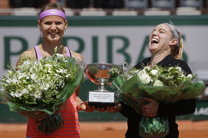 FILE - In this June 7, 2015 file photo, Bethanie Mattek-Sands of the U.S., right, and Lucie Safarova of the Czech Republic, left, hold the trophy after winning the women's doubles final of the French Open tennis tournament. As a professional athlete who is judicious about what she eats and drinks, Bethanie Mattek-Sands knows all too well how impossible it is to avoid the sweet aroma emanating from a stand selling waffles with a chocolate-hazelnut spread just outside the French Open's main stadium. (AP Photo/Thibault Camus, File)