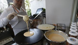A cook prepares crepes at the French Open tennis tournament at the Roland Garros stadium, Friday, June 2, 2017 in Paris. There is nearly constant gastronomic temptation for tennis players at the annual Grand Slam tournament held in one of the world's capitals of cuisine. (AP Photo/Michel Euler)