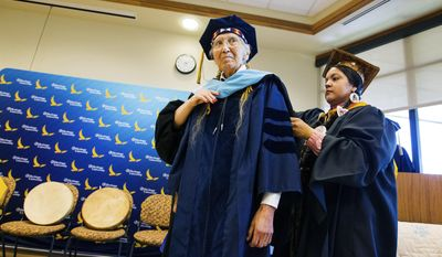 In this Monday, June 5, 2017 photo, Elese Washines, assistant professor at Heritage University and Higher education program manager for the Yakama Nation, performs a hooding ceremony honoring Russell Jim, longtime manager of the Yakama Nation's Environmental Restoration and Environmental Cleanup program, for his influence in Hanford cleanup efforts during a ceremony at Heritage University in Toppenish, Wash. (Shawn Gust/Yakima Herald-Republic via AP)