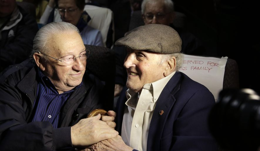 "In this Wednesday, June 7, 2017 photo, Holocaust survivors Israel Arbeiter, left, and Steve Ross, right, greet one another at a theater before the premier of the film ""Etched in Glass: The Legacy of Steve Ross,"" in West Newton, Mass. The film recounts Steve Ross' five years spent in Nazi concentration camps as a child and his decadeslong search for the American soldier who gave him a U.S. flag handkerchief during the liberation of the Dachau concentration camp in Germany. (AP Photo/Steven Senne)"