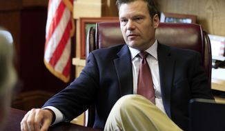 FILE - In this May 17, 2017, file photo, Kansas Secretary of State Kris Kobach talks with a reporter in his office in Topeka, Kan. Kobach, who is helping lead President Donald Trump's commission on election fraud announced Thursday, June 8, 2017, that he's running for the Republican nomination for governor. (AP Photo/Orlin Wagner, File)